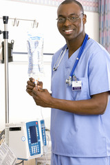 Young male doctor by IV stand, smiling, portrait