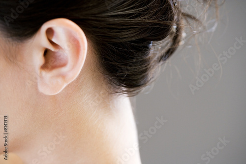 Ear and neck of a woman with dark hair up in a bun