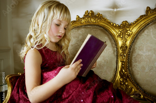 Little girl in a party dress, reading a book