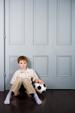 little boy sitting on floor with football