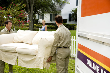 Removal men carrying sofa into new home