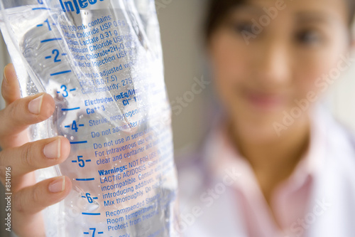 Young female doctor holding IV bag, close-up (focus on bag)