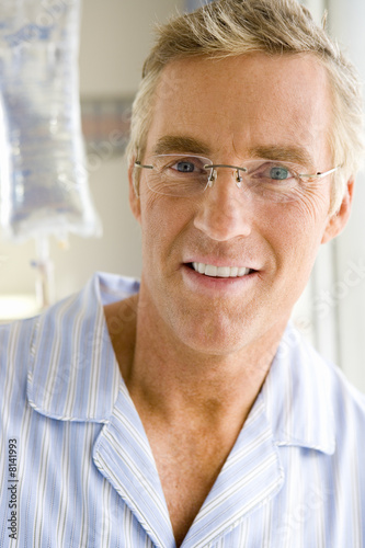 Mature male hospital patient smiling, portrait, close-up, IV bag in background