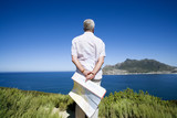 South Africa, Cape Town, senior man holding map, looking out to sea, rear view