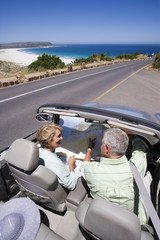 South Africa, Cape Town, senior couple parked on side of road by sea in convertible silver car, looking at map, elevated view