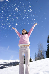 Young woman throwing snow in air in snow field, low angle view