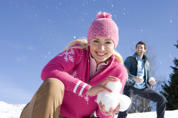 Young woman crouching in snow field, holding snow ball, smiling, portrait, man throwing snow in background