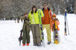 Couple with daughter and son (6-8) standing in snow with skis, smiling, portrait