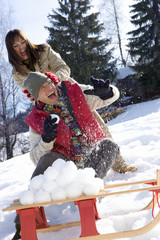 Young couple having snow fight, snow ball pile on sled in foreground