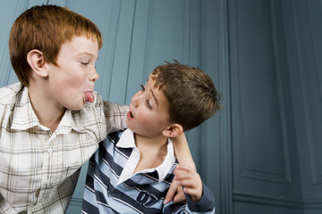 older boy poking tongue out at younger boy