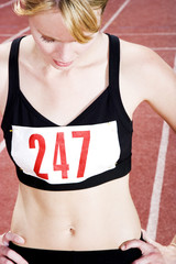 Portrait of a female athlete resting on the running track