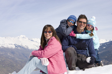 Family of four sitting together in snow field, smiling, portrait