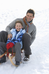 Father and son (7-9) riding sled down snow slope, smiling, low angle view