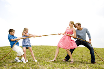family of four playing tug of war