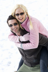 Young couple wearing sunglasses in snow field, man carrying woman on back, smiling, portrait