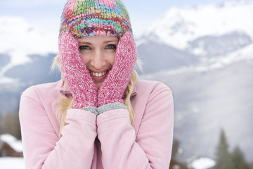 Young woman wearing woolen hat in snow, smiling, portrait, mountain range in background