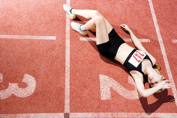 Portrait of a female athlete resting  and sitting on the running track