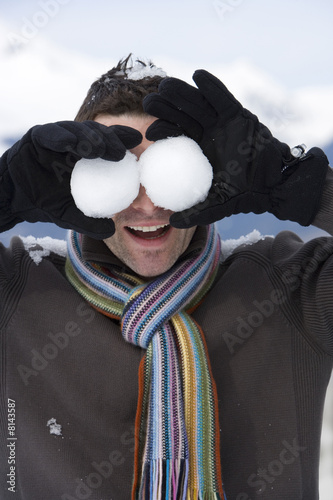 Young man standing in snow field, holding snowballs in front of eyes, close-up
