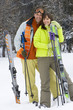 Young couple embracing in snow with skis, smiling, portrait