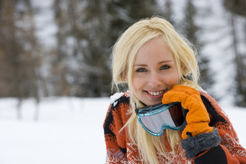 Young woman in snow field, holding ski goggles, smiling, portrait