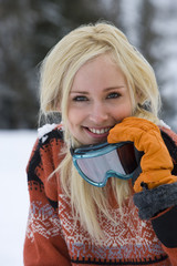 Young woman in snow field, holding ski goggles, smiling, portrait, close-up