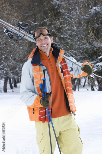 Young man standing in snow with skis, smiling, portrait