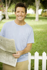 man with newspaper standing in the garden