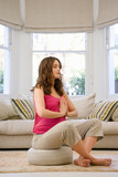 Young pregnant woman meditating on cushion on floor in living room, eyes closed