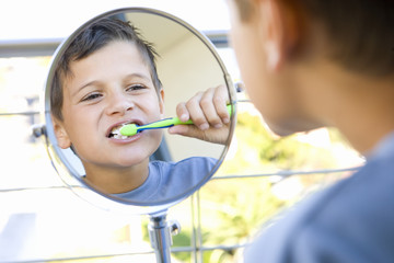 Boy (6-8) brushing teeth in bathroom, looking at reflection in mirror