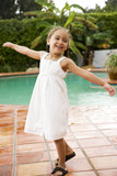 little Hispanic girl dancing on terrace by pool