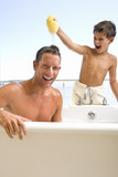 Father and son in bathroom, son (6-8) holding sponge above father's head, smiling