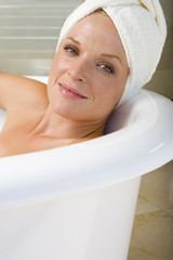 Young woman lying in bath, towel on head, smiling, portrait, close-up