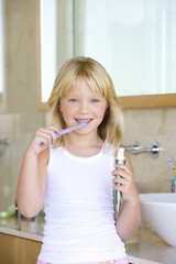 Girl (6-8) brushing teeth in bathroom, smiling, portrait