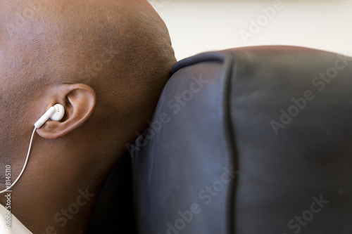 Young man on sofa, wearing earphones, close-up, side view