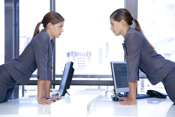 Identical female twins looking at each other over an office desk with computers