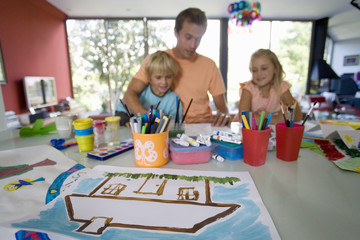 Father with son and daughter (6-8) painting at table, smiling