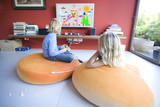 Boy and girl (6-8) sitting on bean bags, watching television, rear view