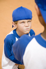 boy glaring at another boy on baseball pitch