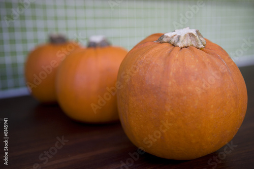 Row of orange Hallowe'en pumpkins on a kitchen counter