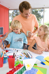 Father standing by son and daughter(6-8) sitting at art and crafts table, smiling at daughter