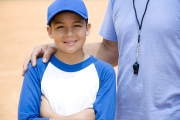 baseball coach with hand on boy's shoulder