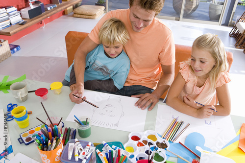 Father sitting with son and daughter(6-8) art and crafts table, smiling, elevated view