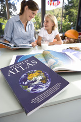 Mother helping daughter (6-8) with geography homework, world atlas in foreground