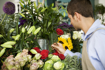 Male florist amongst the flowers in his shop