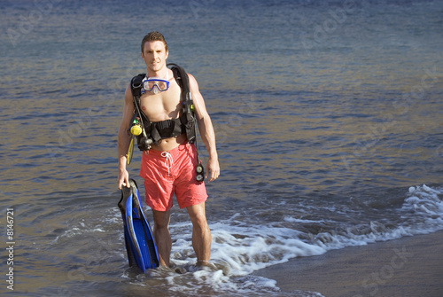 A male scuba diver returning to the shore