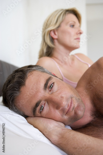 Couple on bed, portrait of man smiling, close-up