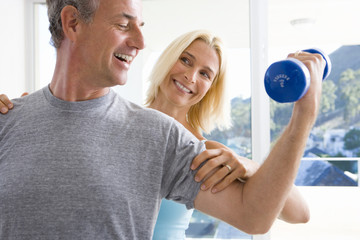 Mature woman smiling at mature man lifting weights, close-up