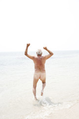 Naked senior man running into the sea