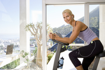 Mature woman riding stationary bicycle indoors, smiling, portrait, side view