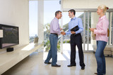 Male real estate agent standing with mature couple in living room, smiling and shaking hands with man
